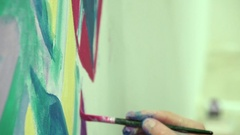 Hand paints with brushes on the wall. Close-up. Slow shooting. Stock Footage