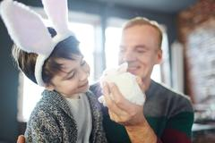 Man showing white fluffy bunny to his son Stock Photos