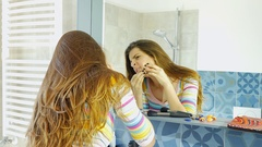 Cute young woman squeezing pimple in front of mirror funny Stock Footage