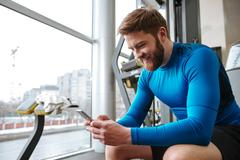 Cheerful young sportsman sitting in gym and looking at phone. Kuvituskuvat