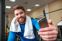 Attractive happy young sportsman make selfie by phone. Kuvituskuvat