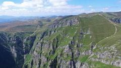 Turists enjoying the view from Caraiman Peak, Romania, aerial flight Stock Footage