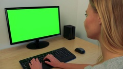 A young woman sits at a desk and works on a computer with a green screen Stock Footage