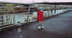 Active baby in red jacket and white sneakers look to soap balloons. He run to Stock Footage
