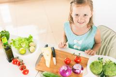 Cute little girl making salad. Child cooking. Healthy food Stock Photos
