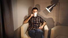 Young man relaxing and drinking coffee sitting on armchair at home Stock Footage