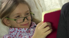 4K Eyeglasses Child Reading Book on Sofa, Girl Portrait Studying in Bed, Coach Stock Footage
