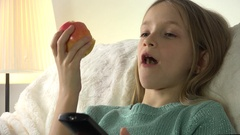 4K Child Eating Apples while Watching TV, Girl Relaxing on Sofa, Coach in Living Stock Footage