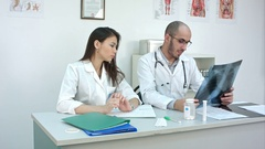 Male doctor teaching his unexperienced female trainee how to analyze xray Stock Footage
