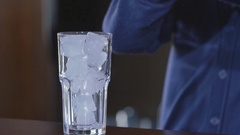 Blue drink pours into glass. Glass with ice and cocktail. Exotic beverage at the Stock Footage