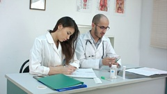 Male doctor counting money and giving it to his female partner Stock Footage