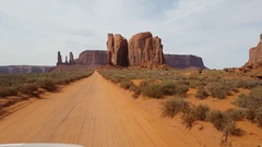 Driving view on a sand road and mountains at a red desert, at monument vall.. Stock Footage