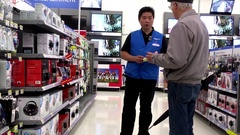 Customer asking clerk about electric appliance questions inside Walmart store Stock Footage