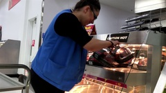 Motion of worker stocking roasted seasoned chickens for sale Stock Footage