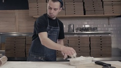 Pizza maker chef is cooking dough at commercial kitchen in moder restaurant for Stock Footage