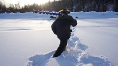 Fisherman with ice screws walking on ice river Stock Footage