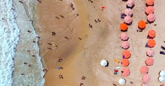 Dreamland beach from aerial top view. Tourists relaxing and surfing, umbrellas Stock Footage