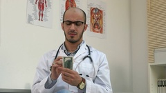 Satisfied male doctor counting money and putting it in his pocket Stock Footage