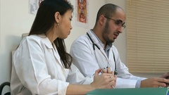 Male doctor teaching his female trainee how to analyze xray image Stock Footage
