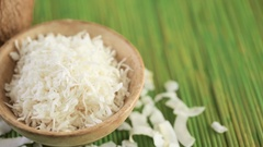 Dehydrated coconut flakes on a wood background. Stock Footage