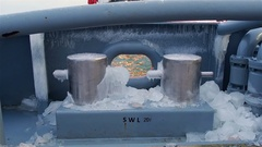 View of ship deck with big pieces of ice on floor and iced metal bollards on it Stock Footage