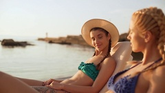 Two beautiful girls talking laughing at the sea side relaxing in chaise lounges Stock Footage