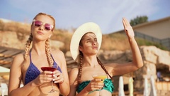 Two beautiful young girls enjoing the sun drinking cocktails at the beach. Slow Stock Footage