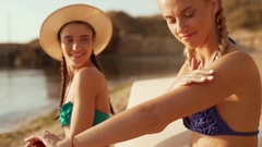 Two beautiful girls at the beach. One is rubbing suntan lotion on her arms. Slow Stock Footage