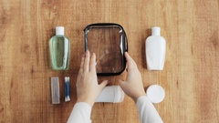 Hands packing bag with cosmetics Stock Footage