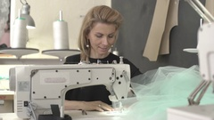 Blonde beautiful Caucasian female sitting at table with sewing machine in Stock Footage