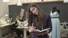 Busy Caucasian brunette young female standing in sewing classroom with notebook Stock Footage