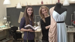 Blonde Caucasian female working on mannequin with azure dress and peach-colored Stock Footage