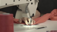 Close up footage of sewing machine stitching piece of peach-colored fabric while Stock Footage