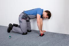 Worker In Overall Lying Carpet Stock Photos