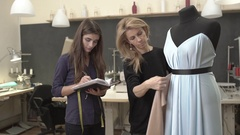 Blonde Caucasian female working with mannequin with azure dress on it while Stock Footage