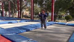 Boy claps hands jumping on trampoline Stock Footage