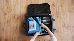 Hands packing travel bag with personal stuff Stock Footage