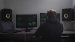 Young hacker with blond hair, dressed in black, sitting in an underground bunker Stock Footage