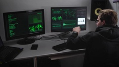 Villain hacker analyzes illegally obtained data on the monitor screens for Stock Footage