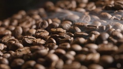 Smoke over a roasted coffee beans on the oven Stock Footage