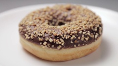 Chocolate donut with nuts on a plate Stock Footage