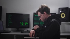 Adult serious man, looking like Hacker, with a small stubble on the face, points Stock Footage