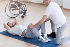 Aged general practitioner stretching the handicapped in the sports hall Stock Photos