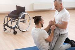 Helpful orthopedist assisting the handicapped in the gym Stock Photos