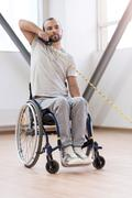 Concentrated young handicapped stretching the cable in the gym Stock Photos