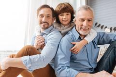 Nice delighted boy hugging his family Stock Photos