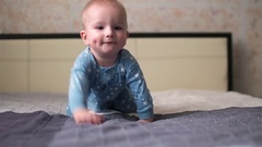 Lovely smiling baby boy with dimples on cheeks and in star pyjamas crawling on Stock Footage