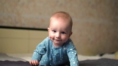 Cute smiling baby boy with dimples on cheeks and in star pyjamas crawling on bed Stock Footage