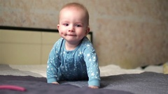 Adorable baby boy in star pyjamas crawling on bed. Closeup Stock Footage