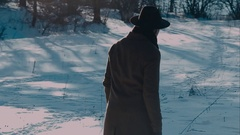 A man in a felt hat and coat comes in the winter woods. brown hat made of felt Stock Footage